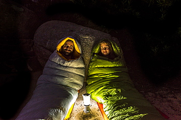 Man and a woman in sleeping bags smiling lit by a lantern at night.