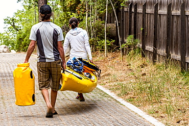 Two people carrying a kayak and drybags down an alley.