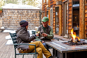 Couple toasting one another outside by a firepit at the lodge