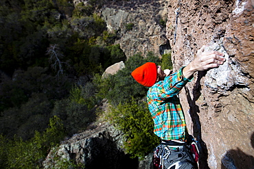 A male climber in an orange beanie and multicolored shirt climbs Family Jewel (5.10d) on Mount Gorgeous in Malibu Canyon State Park in Malibu, California.  Family Jewel is a very popular sport climb in Malibu Canyon.
