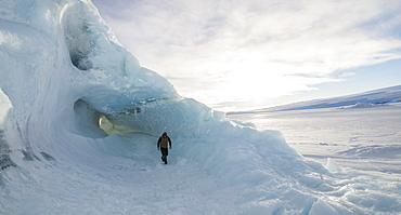 A man exploring an iceberg frozen into the surface of the McMurdo Sound in the Ross Sea Region of Antarctica.