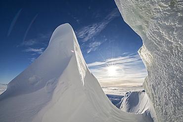 Sun shines through a crack in an iceberg in McMurdo Sound on the Ross Sea, Antarctica.