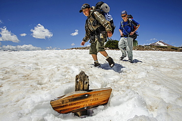 Boys hike past a trail sign buried in a late melting snow field, at about 11,000 feet below Tungsten Pass, on the fourth day of Troop 693's six day backpack trip through the High Uintas Wilderness Area, Uintas Range, Utah