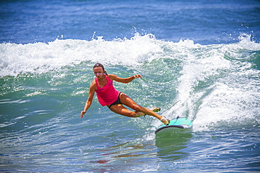 Surfer girl catches wave in high heels.