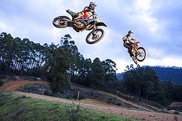 Two dirt bike riders jump a tabletop at the same time during a race at Blackwood park.