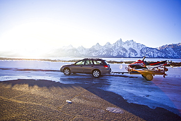 Parked in front of Tetons, a station wagons pulls an older snowmobile on a trailer just before sunset.