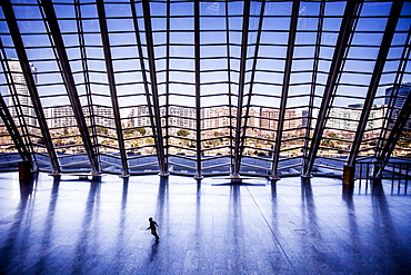 Child running across an empty floor at a museum.