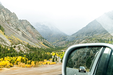 Side mirror view driving up Tioga Pass in a storm
