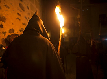 A penitent dressed as a Benedictine monk holds a torch at the procession of the Black Christ of Santa Maria during Easter Holy Week inside of the Cathedral of Caceres, Extremadura, Spain