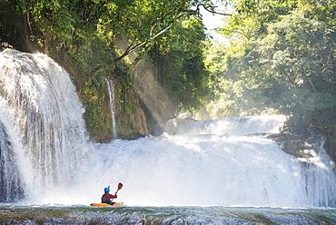 One man on his kayak below some waterfalls in Cascadas de Agua Azul, Chiapas, Mexico.