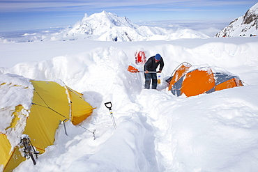 A mountain ranger is digging out tents after a snowstorm covered them during the night in 14k camp on Mount McKinley, Alaska.     Climbers are advised to spare no expense on a expedition-quality tent as it can mean the difference between life and death during a ferocious storm on Denali.     Extra poles and repair materials are important in case of damage caused by storms. Plan to take extra pickets, wands or deadmen for tent anchors. Never leave a tent without anchoring it securely. Tents are lost each year due to sudden gusts of wind while the tent was left unattended or drying.     Every climbing season High Mountain Rangers of the Denali National Park Service are called to help climbers in need. If possible the patient is brought down to base camp on foot, only in life threatening conditions a helicopter is called to evacuate the patient to a hospital in Anchorage.