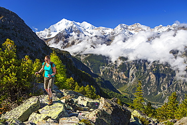 A female hiker on her way to the Wannihorn, a mountain peak in the Swiss Alps, close to Zermatt. In the background is the Weisshorn range. This region of Wallis is home to over 40 of 4000 meter peaks and a paradise for outdoor enthusiasts like climbers, hikers, mountainbikers, trailrunners and nature lovers.