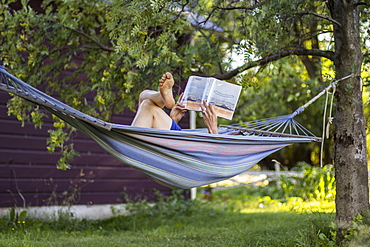 Woman reads a book in her hammock on her ranch during summer in Montana.