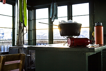 Melting snow on a camp stove in an old fire lookout in Montana.
