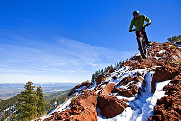 A man rides his fat tire bike along a partially snow covered rocky section of the Crest Trail in Big Cotton Wood Canyon, Utah.