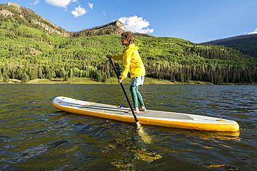 A girl stand up  paddleboarding on Lake Humphreys, Creede, Colorado.
