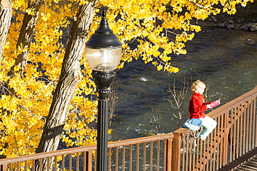 A young girl reading a book while sitting on a bridge over the Animas River on the Animas River Trail in Durango, Colorado.