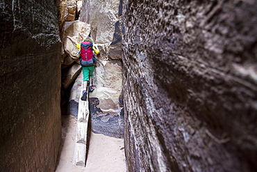 A young girl  backpacking along the Chessler Park and Joint Trail in the Needles District of Canyonlands National Park, Monticello, Utah.