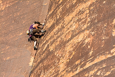 A woman rock climbing up a layback crack at a rock climbing area called The Wall in Indian Creek, Monticello, Utah.