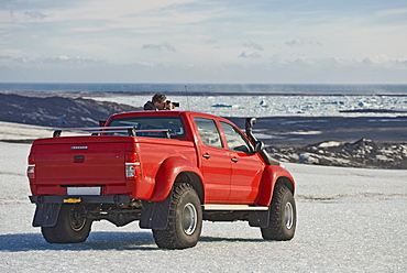Man stopping and taking a picture from a customised Icelandic 4x4 pick up truck on the Breidamerkurjokull glacier, which is a part of the Vatnajokull glacier