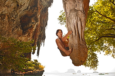 woman bouldering on limestone stalagtite at Railay beach in Thailand