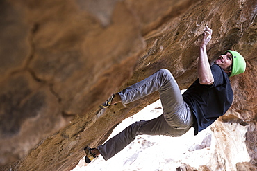 Professional male climber bouldering in Hueco Tanks, Texas during the Hueco Rock Rodeo