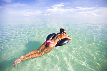 A young woman floats on an inflatable water toy in shallow turquoise water while on vacation in Cayo Coco, Cuba.