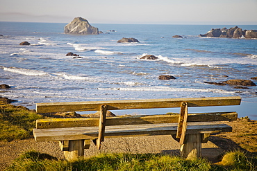 An old weathered wooden bench looks out at Bandon Bay, Oregon.