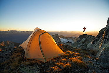 A silhouetted hiker stands on a rock bluff while camping on the summit of Saxifrage Peak, Pemberton, BC, Canada.