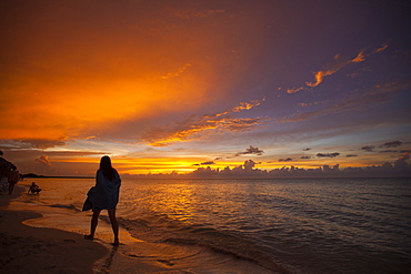 A silhouetted young woman wrapped in a towel walks the beach just after sunset in Cayo Coco, Cuba.