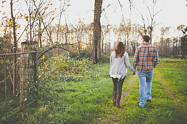 A couple hold hands while walking  along an old farm road.