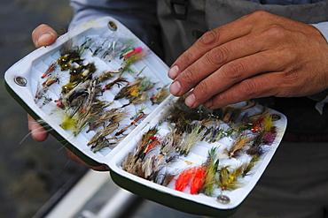 A fly fisherman examines his fly box.