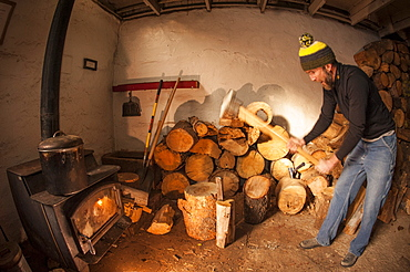 Man splitting firewood inside the Peter Grubb Hut, Sierra Nevada