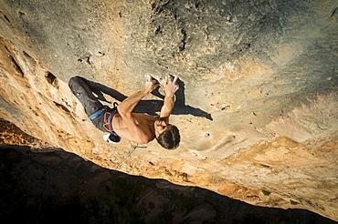 A man climbing 'La tentación de seguir,' a hard route full of monofinger in Sierra de Guara