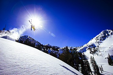 A man does a backflip off a jump in the Brighton Utah backcountry.