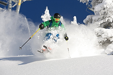 A man skiing powder on a beautiful sunny day in Utah.