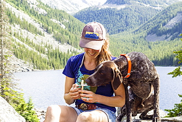 Woman shares her string cheese with her dog while on a hike in Montana