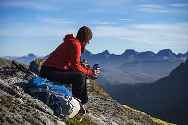 Female hiker takes a break and enjoys mountain views, Moskenesøy, Lofoten Islands, Norway