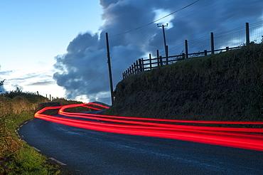Car streaks on the narrow hillside roads of Dingle