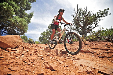 Woman rides the Submarine Rock Loop in South Sedona, Arizona. The trail has everything from slickrock to single track to stairs that lead to Submarine Rock.