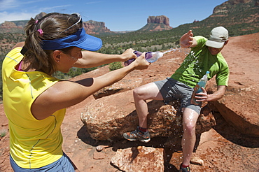 Couple plays with water bottles the Cathedral Rock Trail in Sedona, Arizona. The trail over slick rock sandstone leads to a popular group of spires above Sedona.