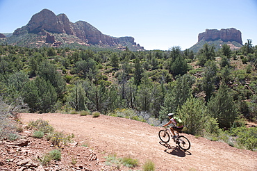 Woman rides the popular Bell Rock Pathway near Courthouse Butte in South Sedona, Arizona.  Bell Rock Pathway is a popular starting point to access Sedona's classic loop rides.
