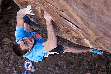Rock climber on steep overhanging boulder during the Hueco Rock Rodeo in Hueco Tanks State Park, Texas