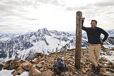 A hiker poses beside the summit post of Frosty Peak, British Columbia, Canada.