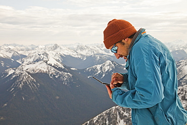 A hiker checks his text messages while standing on the summit of a mountain.