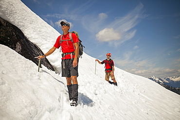 Two climber cross a snowfield high in the mountains of British Columbia, Canada.