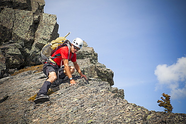 A climber carefully down climbs a rocky summit in British Columbia, Canada.