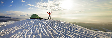 A climber poses beside his tent the morning after camping on the snow in the mountains of British Columbia, Canada.
