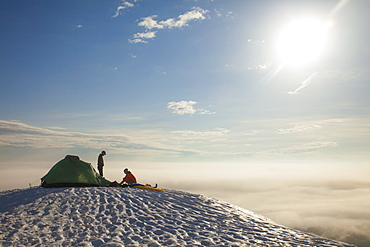 Two climbers sort their gear out beside their tent while camping in the mountains of British Columbia, Canada.