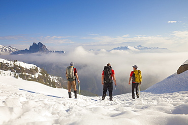 Three backpackers cross a snowfield after a trip into the mountains of British Columbia, Canada.